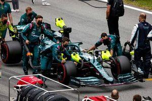 Los mecánicos mueven a Lance Stroll, Aston Martin AMR21, a su posición en la parrilla