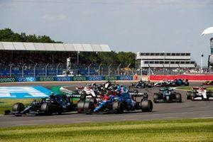 Sebastian Vettel, Aston Martin AMR21, Fernando Alonso, Alpine A521, Carlos Sainz Jr., Ferrari SF21, and the remainder of the field on the restart