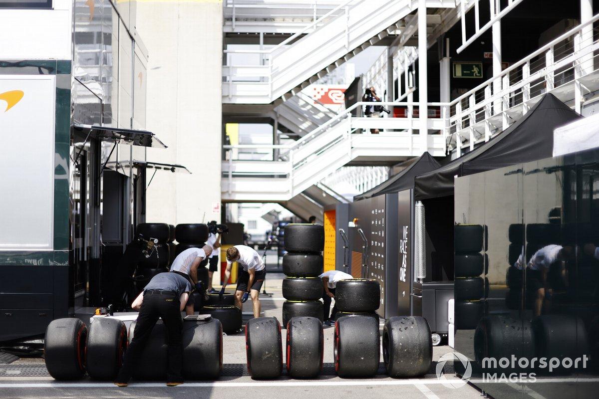 Mechanics wash tyres in the paddock