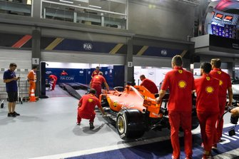 Ferrari SF90 being pushed into the scrutineering bay by Ferrari mechanics