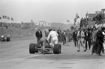 Graham Hill spingono la Lotus 49 Ford in pit lane, al GP d'Olanda del 1967