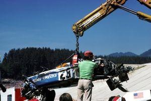Los restos del Penske Racing Cars March 751 de Mark Donohue son retirados después de su choque en la curva de Hella Licht durante la práctica