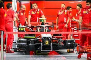 Ferrari mechanics in the garage with one of their cars