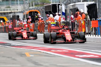 Charles Leclerc, Ferrari SF90, leads Sebastian Vettel, Ferrari SF90, in the pit lane