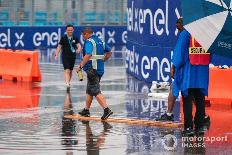 Oficial de pista camina por la pista mojada