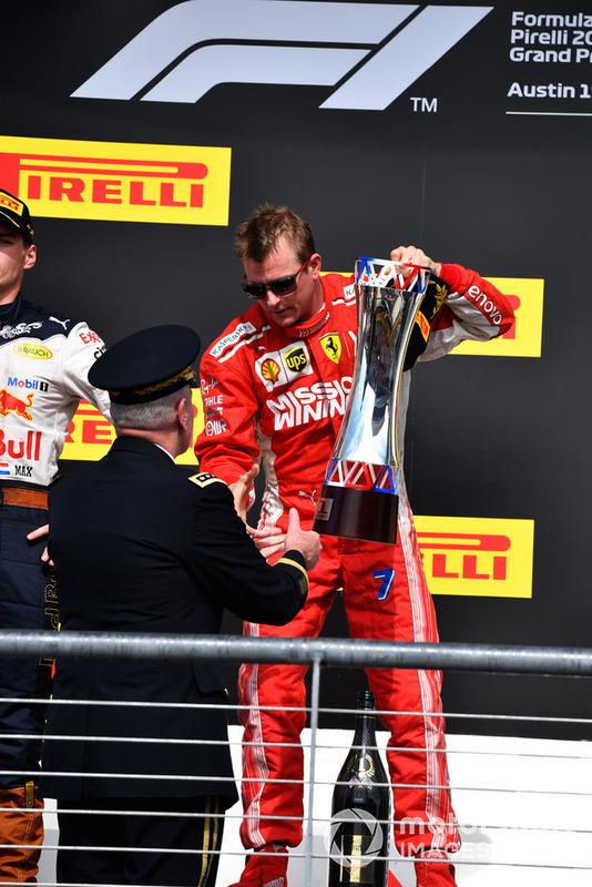 Kimi Raikkonen, Ferrari receives the race winners trophy on the podium