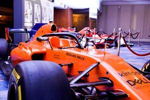 Una monoposto McLaren di F1 e delle monoposto di F2 esposte accanto alla lista dei candidati al