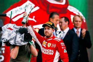 Sebastian Vettel, Ferrari, 2° classificato, alza il suo trofeo sul podio