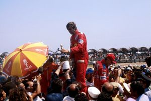 The podium (L to R): Emerson Fittipaldi, Fittipaldi, second (Obscured by umbrella); Carlos Reutemann, Ferrari, winner; Niki Lauda, Brabham, third