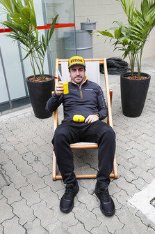 Fernando Alonso, McLaren, holds a drink while sitting on a deckchair for RTL