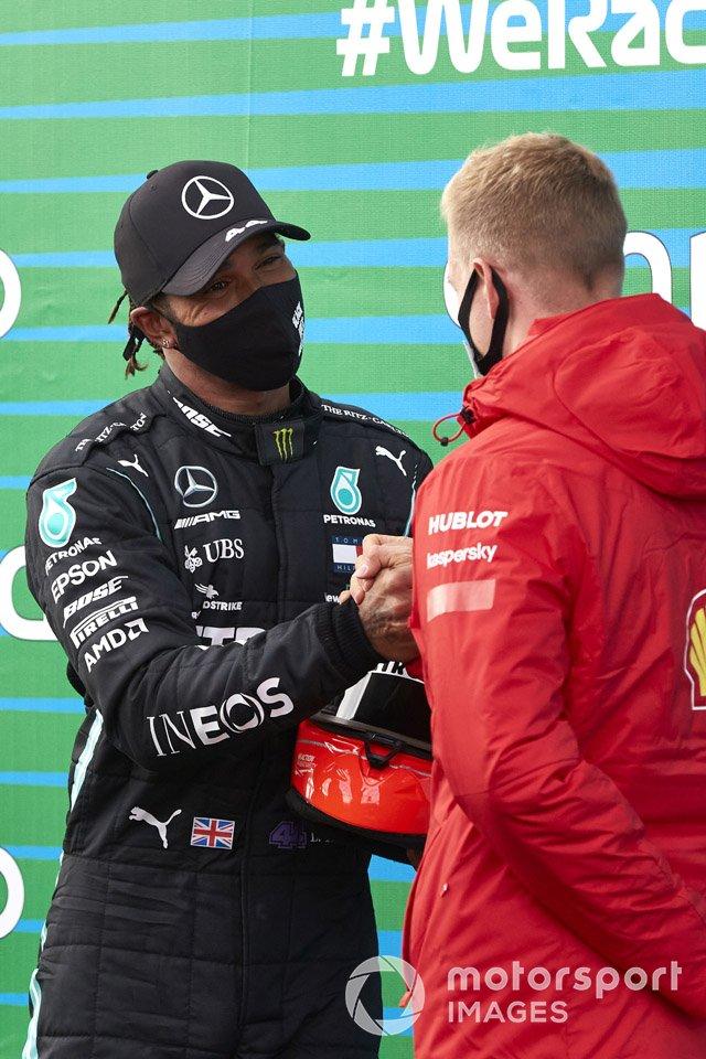 Mick Schumacher entrega a Lewis Hamilton, Mercedes-AMG F1, el casco de su padre después de que el piloto de Mercedes igualara el récord de Michael Schumacher de 91 victorias en carreras