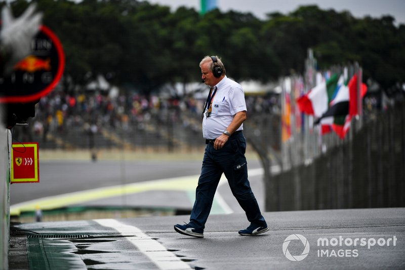 A member of the FIA walks across the pit lane