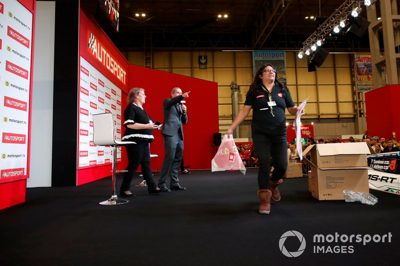 Presenter Stuart Codling directs members of the Autosport team to throw Ferrari merchandise out into the crowd