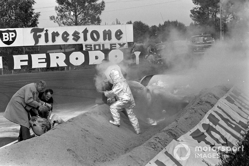 Marshals and fire crew put out the lazing car of Mike Salmon, Brian Redman
