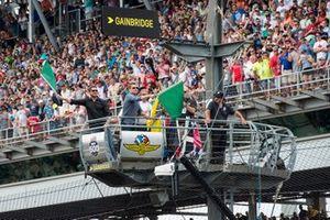 Актеры Кристиан Бейл и Мэтт Деймон машут зелеными флагами, давая старт гонке «Инди 500»