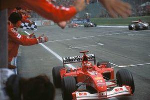 Michael Schumacher, Ferrari F2002, passa sotto alla bandiera a scacchi e festeggia con il team Ferrari