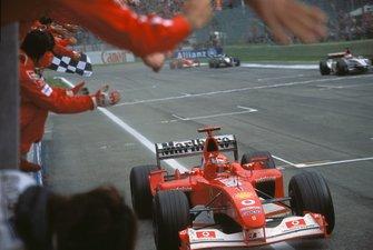 Michael Schumacher, Ferrari F2002, takes the chequered flag and celebrates with the Ferrari team