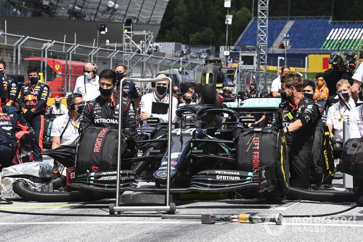 Los miembros del equipo Mercedes se arrodillan en la parrilla