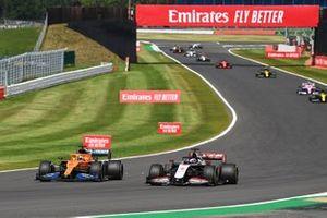 Carlos Sainz Jr., McLaren MCL35, battles with Romain Grosjean, Haas VF-20