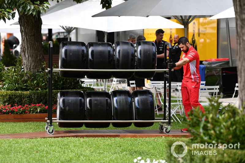 A Ferrari team member pushes a trolly of tyres