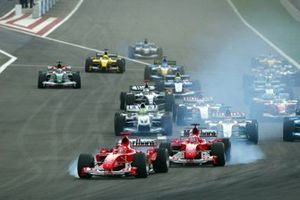 Michael Schumacher, Ferrari F2004 and Rubens Barrichello, Ferrari F2004 both lock up at the start of the race