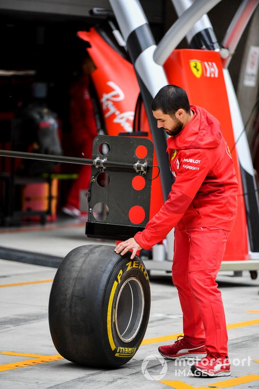Ferrari Mechanic with Pirelli tyre in pit lane