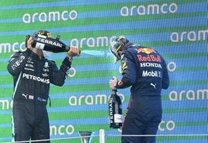 Lewis Hamilton, Mercedes, 1st position, and Max Verstappen, Red Bull Racing, 2nd position, spray Champagne on the podium