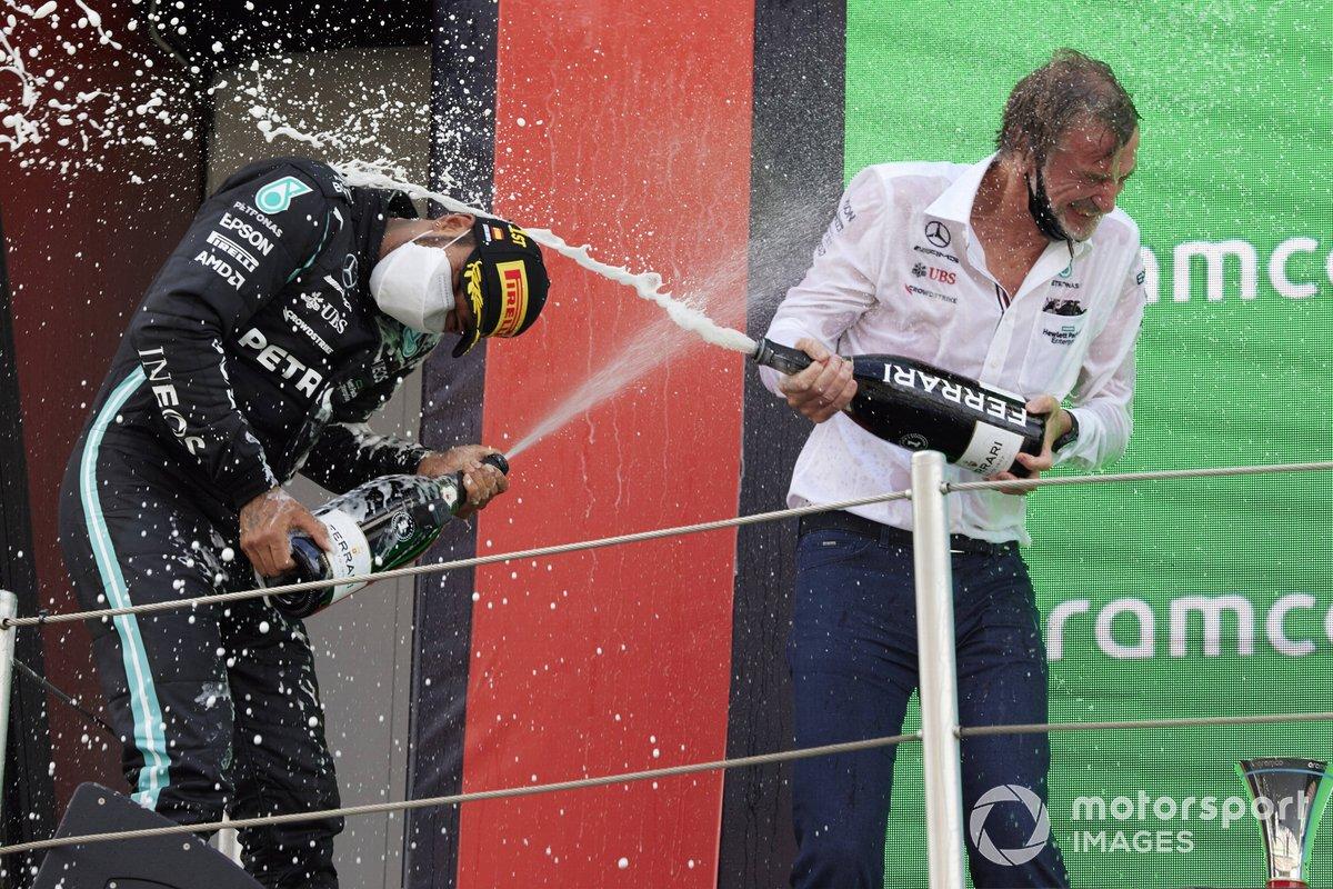 Lewis Hamilton, Mercedes, primera posición, y el encargado de Mercedes de recoger el trofeo se bañan con champán en el podio.