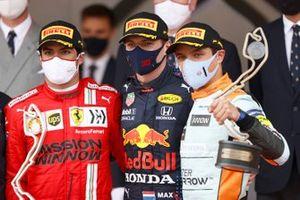 Carlos Sainz Jr., Ferrari, 2nd position, Max Verstappen, Red Bull Racing, 1st position, and Lando Norris, McLaren, 3rd position, on the podium