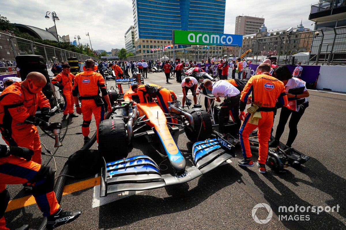 Mecánicos en la parrilla con el coche de Daniel Ricciardo, McLaren MCL35M