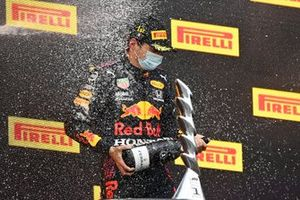 Lewis Hamilton, Mercedes, 2nd position, and Max Verstappen, Red Bull Racing, 1st position, spray Champagne on the podium