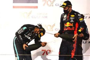 Lewis Hamilton, Mercedes-AMG F1, 1st position, and Alex Albon, Red Bull Racing, 3rd position, celebrate on the podium with Champagne
