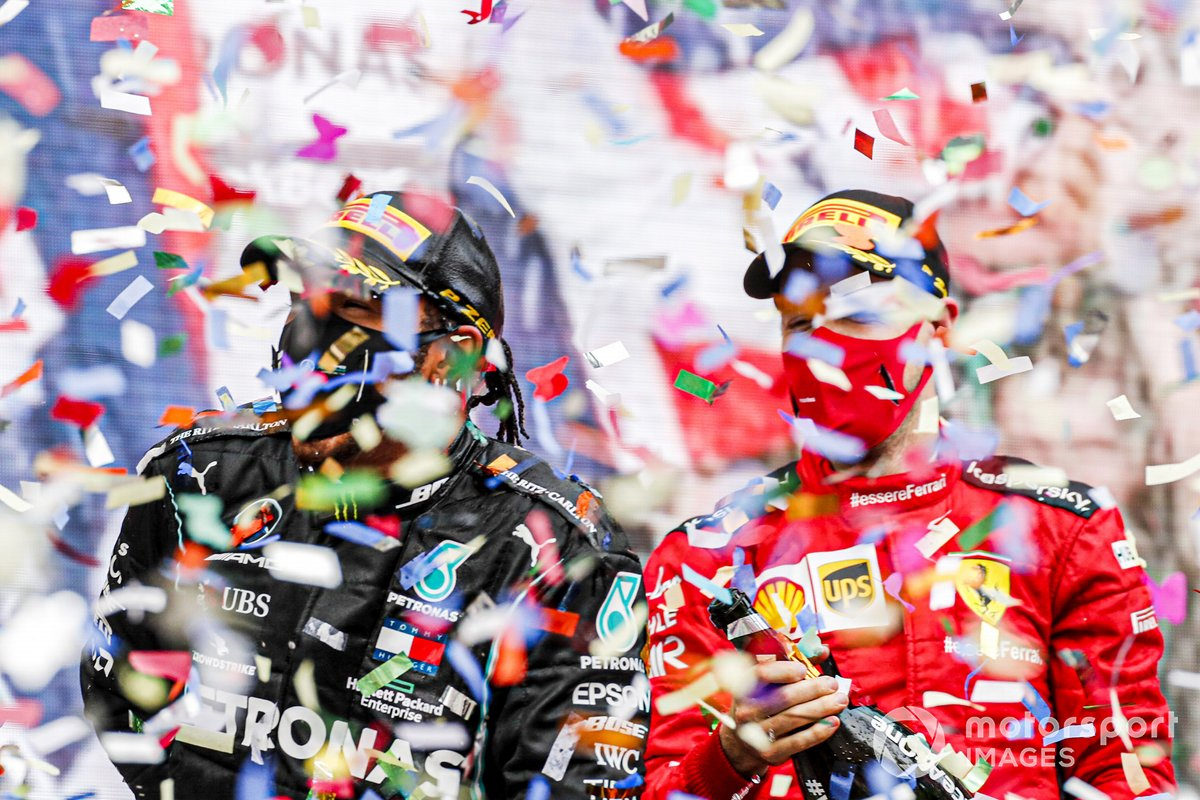 Lewis Hamilton, Mercedes-AMG F1, 1st position, and Sebastian Vettel, Ferrari, 3rd position, celebrate with Champagne on the podium