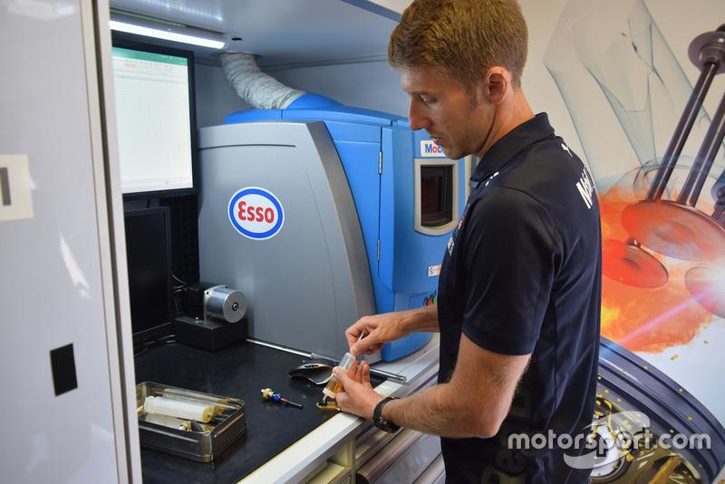 Ingegnere Exxon-Mobil al lavoro nel laboratorio mobile all'interno del box Red Bull