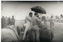 Während einer Trainingspause zum GP von Südafrika 1937 in East London wird der Alfa Romeo 8C 3800 von Hans Rüesch (links) bei Regen getankt. Beim Alfa Romeo handelt es sich um ein ehemaliges Fahrzeug der Scuderia Ferrari