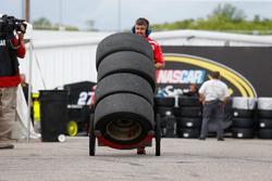 Un homme se cachant derrière des pneus, mais il en manque un