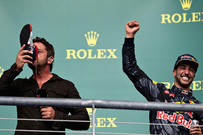 """L'acteur Gerard Butler fait un """"shoey"""" sur le podium aux côtés de Daniel Ricciardo, Red Bull Racing"""