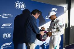 Lewis Hamilton, Mercedes AMG F1, signe un pneu Pirelli miniature après sa pole position