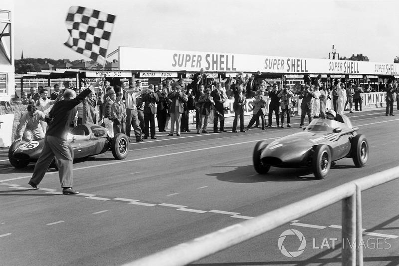 Стирлинг Мосс за рулем Vanwall пересекает финишную черту Гран При Великобритании. Взмах клетчатого флага принес победу не только ему, но и его партнеру по команде и машине Тони Бруксу
