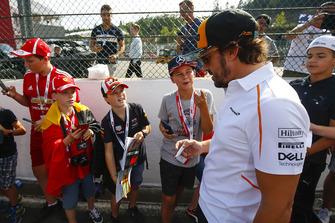 Fernando Alonso, McLaren, signs autographs for young fans