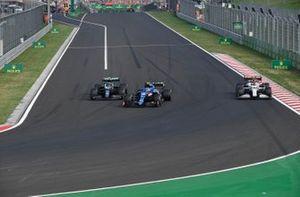 Esteban Ocon, Alpine A521, Sebastian Vettel, Aston Martin AMR21, as they lap Antonio Giovinazzi, Alfa Romeo Racing C41