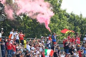 Fans with a red smoke flare in a grandstand