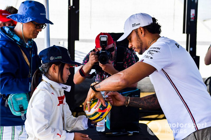 Lewis Hamilton, Mercedes AMG F1 signs a mini helmet for a fan