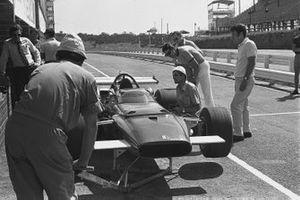 Un meccanico lavora sulla Ferrari 312B ai box mentre Jo Siffert li osserva, Gp del Sud Africa del 1970