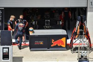 Alex Albon, Red Bull Racing, talks to colleagues outside of the team's pit garage