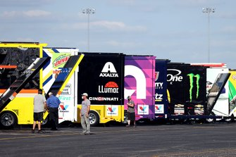 NASCAR Cup Series haulers are unloaded in the garage area