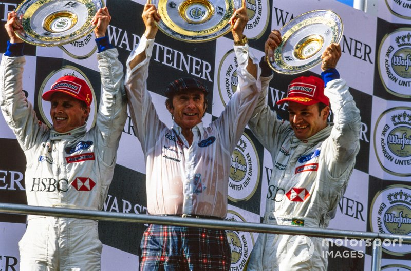 Race winner Johnny Herbert, Jackie Stewart, Team Principal, Stewart Grand Prix, and Rubens Barrichello, 3rd place, celebrate on the podium