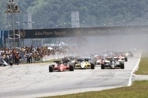 Michele Alboreto, Ferrari 126C4, leads Nigel Mansell, Lotus 95T Renault, and Derek Warwick, Renault RE50, at the start