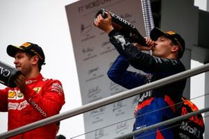 Sebastian Vettel, Ferrari, 2nd position, and Daniil Kvyat, Toro Rosso, 3rd position, celebrate with Champagne on the podium