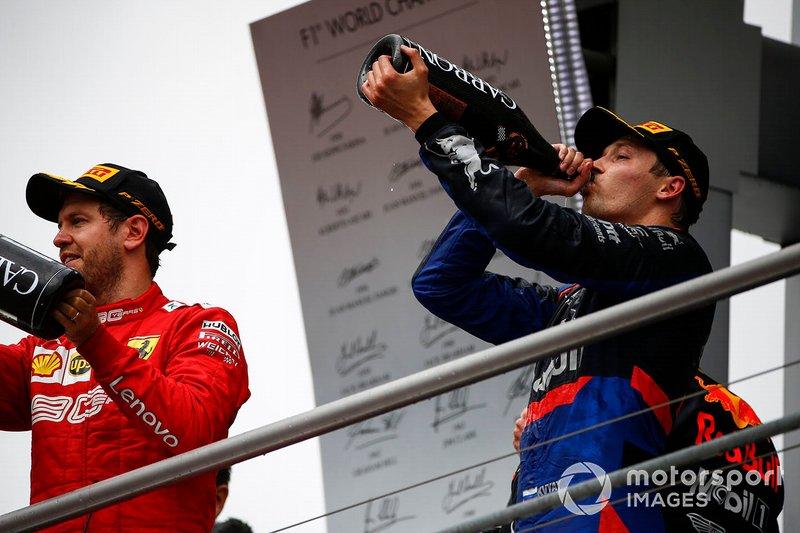 Sebastian Vettel, Ferrari, 2° classificato, e Daniil Kvyat, Toro Rosso, 3° classificato, festeggiano sul podio, con lo Champagne